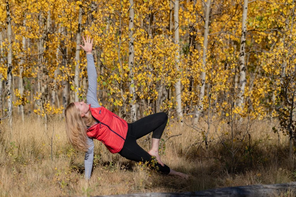 Side plank pose in front of aspen trees in Colorado
